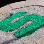 """Green and white fire glass accents the propane-powered fire pit. The green """"S"""" stands for Spartans, the mascot for Michigan State University where Richard and Julie first met and attended college."""
