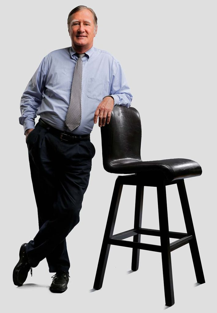 man-standing-next-to-chair