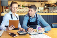 two-people-at-desk-in-market